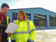 Electrical Contractor Paul Beattie, owner & director of Solar Electrics, (left) and Caroline Moody, Managing Director of Moody Logistics (right) review the plans to the new Cross-Desk facility under construction at the company's base in Northumberland
