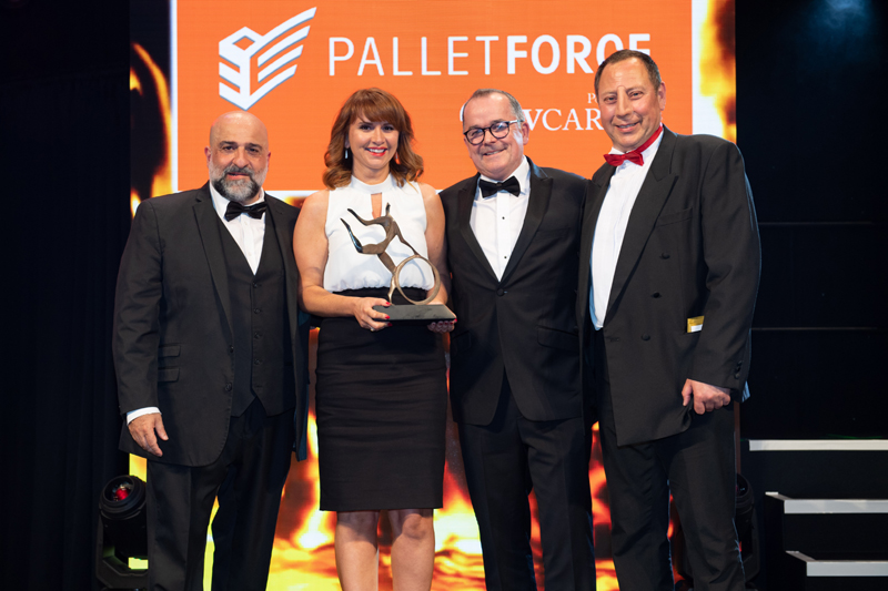 Michael Conroy, CEO of sponsor Palletforce, presenting the trophy to Arrow XL director of people services Zoe Sinclair, with comedian Omid Djalili (far left) and MT editor Steve Hobson (far right)
