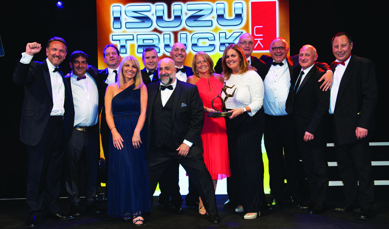 Syan Hancock, general manager of care (fourth left) at sponsor Isuzu Truck UK, presents the trophy to Dwain McDonald, CEO (far left), Sinead Croke, director of customer experience (fifth right), and the team at DPD UK