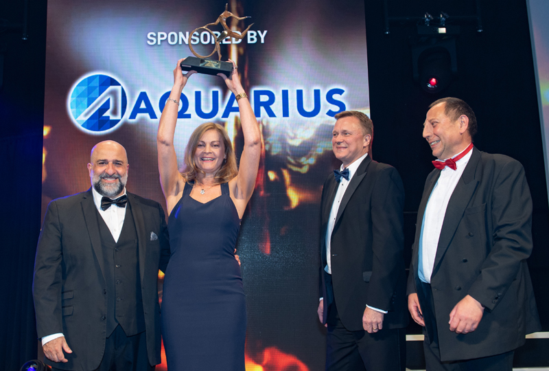 Guy Reynolds, commercial director of sponsor Aquarius (second right), presents the Service to Industry Award to Carole Walker, accompanied by comedian Omid Djalili (far left) and MT editor Steve Hobson