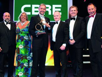 Simon Doughty (second right), business unit director at sponsor CBRE, presents the Apprenticeship of the Year trophy to Michael Errington (third left), head of HR and training at Nagel Langdons